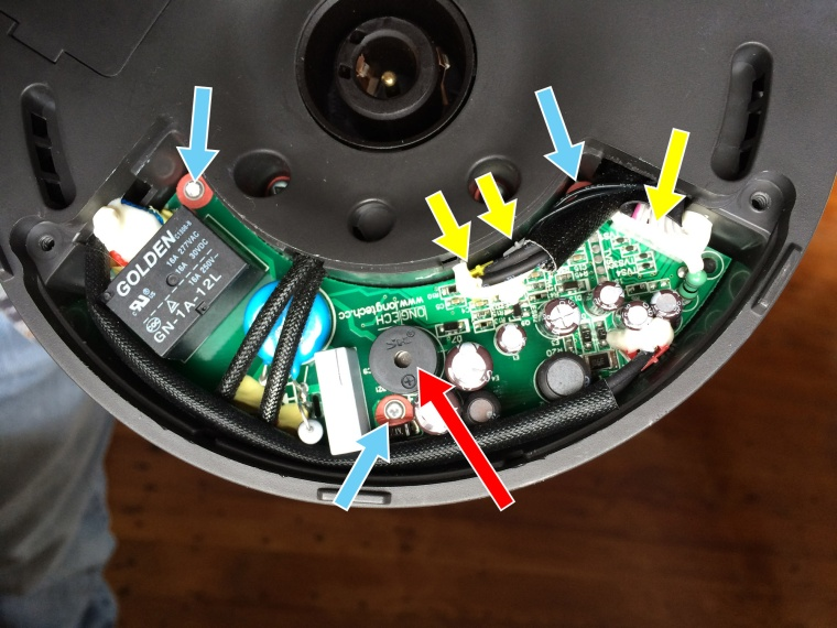 The main circuit board exposed, showing the offending piezo buzzer (red arrow), the three screws that need to be removed (blue arrows) and the three connectors that need to be pulled out (yellow arrows)